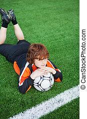 liten pojke, med, fotboll, lögnaktig, på, fält