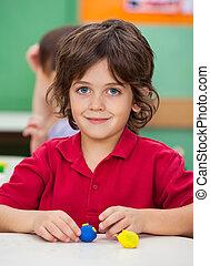 liten pojke, med, lera, på skrivbordet