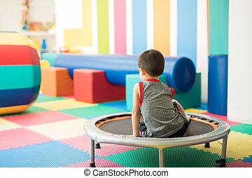 liten pojke, sittande, på, a, trampolin