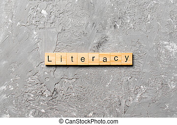 LITERACY word written on wood block. LITERACY text on cement table for your desing, concept