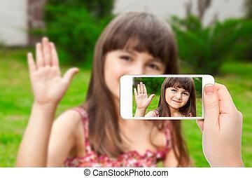 litet, kvinnlig, rop, avskärma, hand, ringa, grön fond, holdingen, video, flicka, gräs