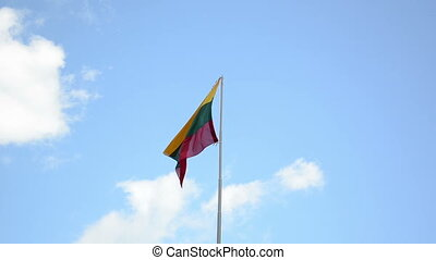 Tricolor Lithuania national flag move in wind on background of blue cloudy sky.
