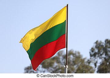Lithuanian flag flying on flagpole on blue sky background