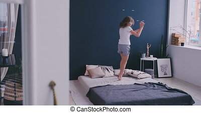 Litl girl Dancing on bed and listening to music with...
