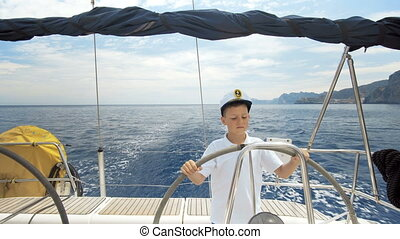 Litle children captain at the helm controls of a sailing...