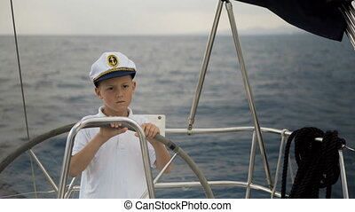 Litle children skipper at the helm controls of a sailing...