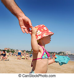Litlle girl holding her fathers hand at the beach