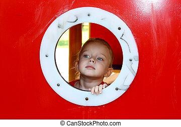 Litlle girl looking through circle window