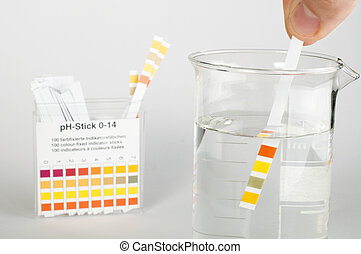 Litmus strips for measurement of acidity.Beaker with water