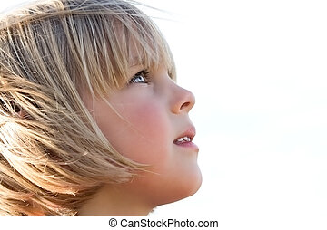Pretty little girl staring upwards in awe with wind blowing her hair