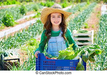 Litte kid farmer girl in vegetables harvest