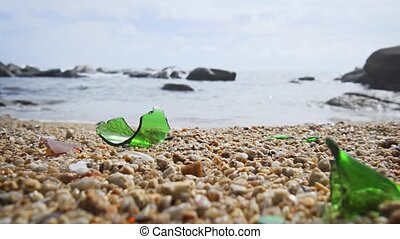 Shards of broken glass from a green bottle present a hazard on this otherwise pristine, tropical beach. UltraHD 4k video