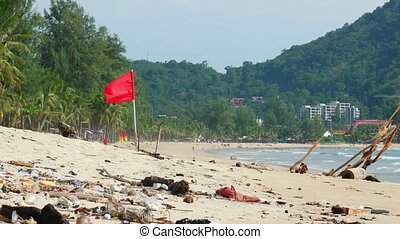 Red safety flag, flapping in the breeze over a polluted and litter strewn, tropical tourist beach in Thailand, with luxury beach hotels and forested hills in the background.