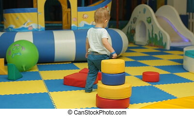 little 2 year old toddler boy playing with pyramid