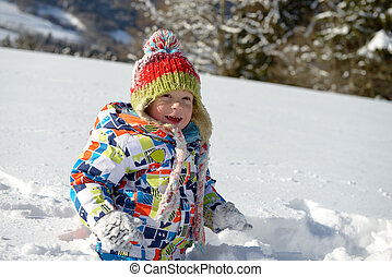 little 3 year old child playing in the snow