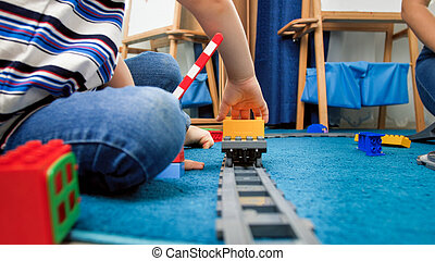 Little 4 years old boy sitting on carpet and playing with toy trains