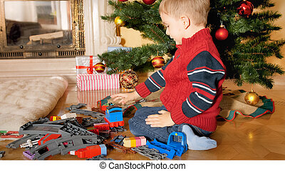 Little 4 years old boy sitting on floor under Christmas tree and building toy railroad