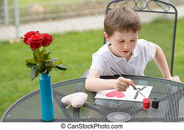 7 year old boy paints greeting card for Mom
