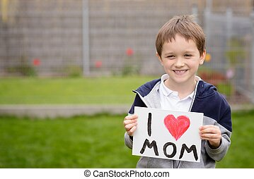 7 years boy holding a greeting card for his mother