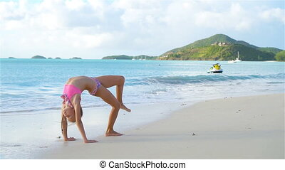 Little active girl making cartwheels on white beach....
