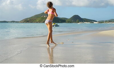 Little active girl making cartwheels on white beach.