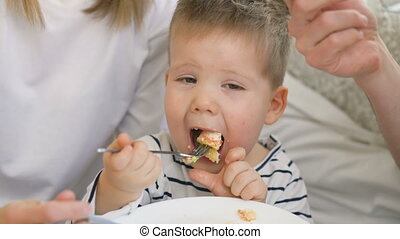 Little adorable boy celebrating his birthday with father and mother eat cake and drink tea