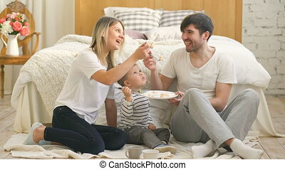 Little adorable boy celebrating his birthday with father and mother eat cake in bedroom