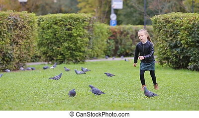Little adorable girl chasing pigeons on grass in a warm autumn day