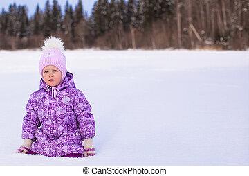 Little adorable girl enjoying snow winter sunny day