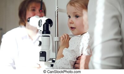 Little adorable girl in child's ophthalmology - optometrist...