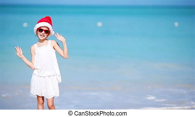 Little adorable girl in Christmas hat on white beach during...