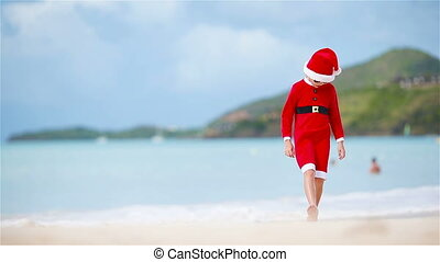 Little adorable girl in Christmas hat on white beach during Xmas vacation