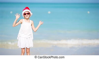 Little adorable girl in Christmas hat on white beach having fun on Xmas vacation