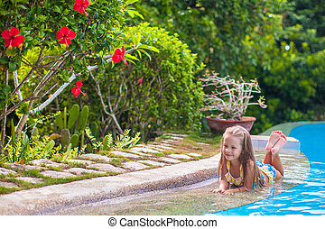 Little adorable girl in the swimming pool looks at camera