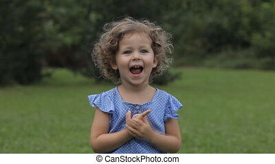 Little adorable girl is talking and shows the tongue, look...