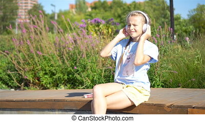 Little adorable girl listening music in the park outdoors