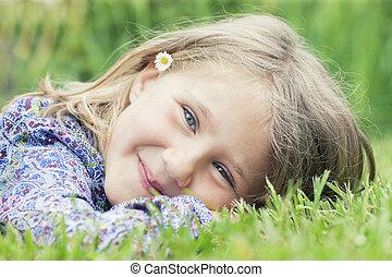 girl lying on grass smiling