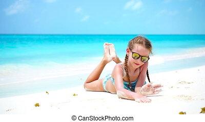 Little adorable girl on the white beach