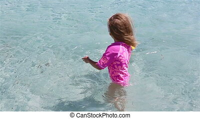 Little adorable girl playing during tropical vacation. Kid have fun with beach toy in shallow water