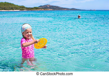 Little adorable girl playing frisbee during tropical vacation