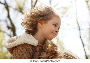 Little adorable girl sitting on her mother's shoulders. Autumn outdoor.