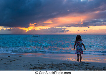 Little adorable girl walking in the sunset on a tropical beach