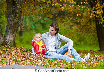 Little adorable girl with happy father in autumn park outdoors
