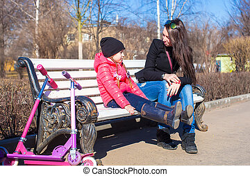 Little adorable girl with her mother on sunny day outdoors