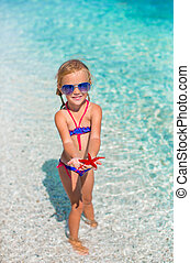 Little adorable girl with sea star at the tropical beach