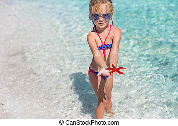Little adorable girl with sea star in her hands at the tropical beach