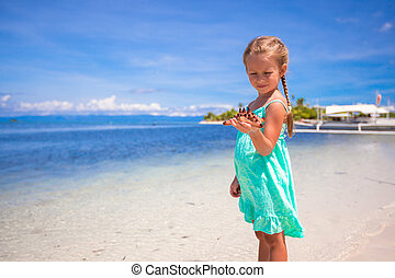 Little adorable girl with starfish in her hands at the tropical beach