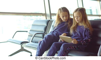 Little adorable girls in airport waiting for boarding and playing with laptop