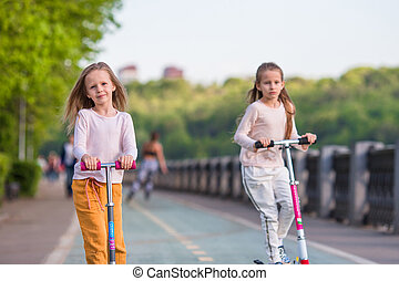 Little adorable girls riding on scooters in park outdoors
