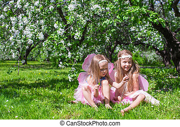 Little adorable girls with butterfly wings in the blossoming apple orchard